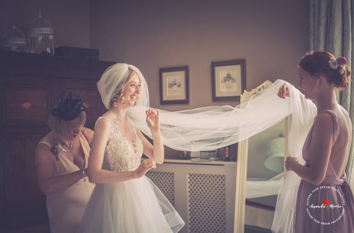 bride prep in wedding dress photograph