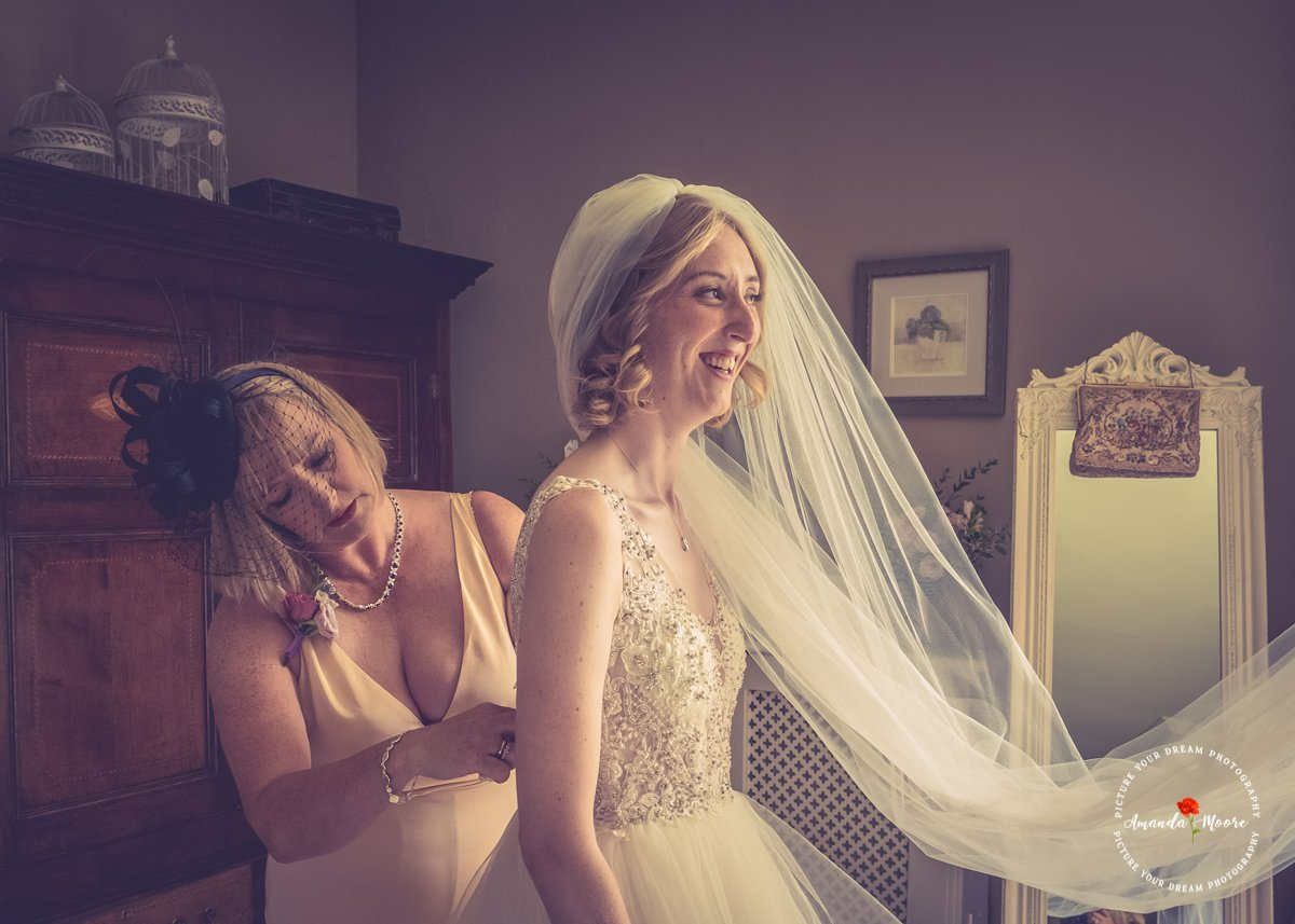 Bride putting her wedding dress on