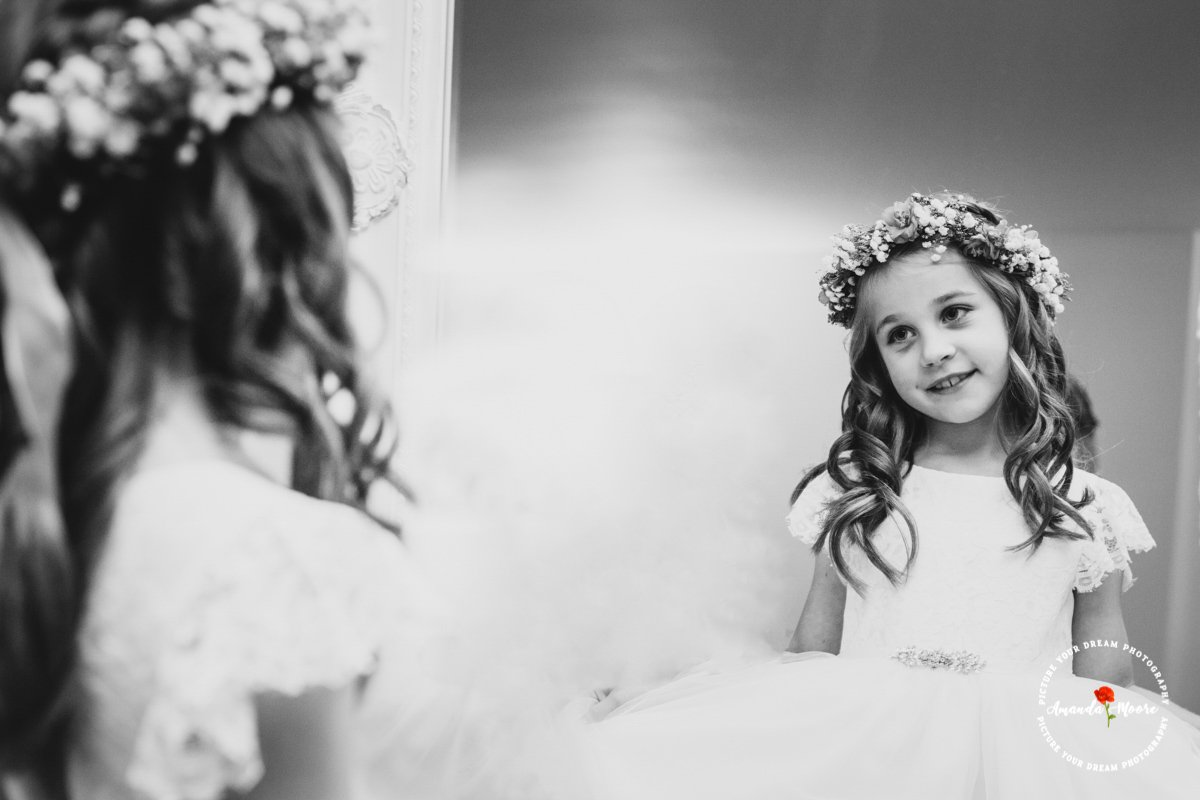 Little girl looking in mirror at wedding