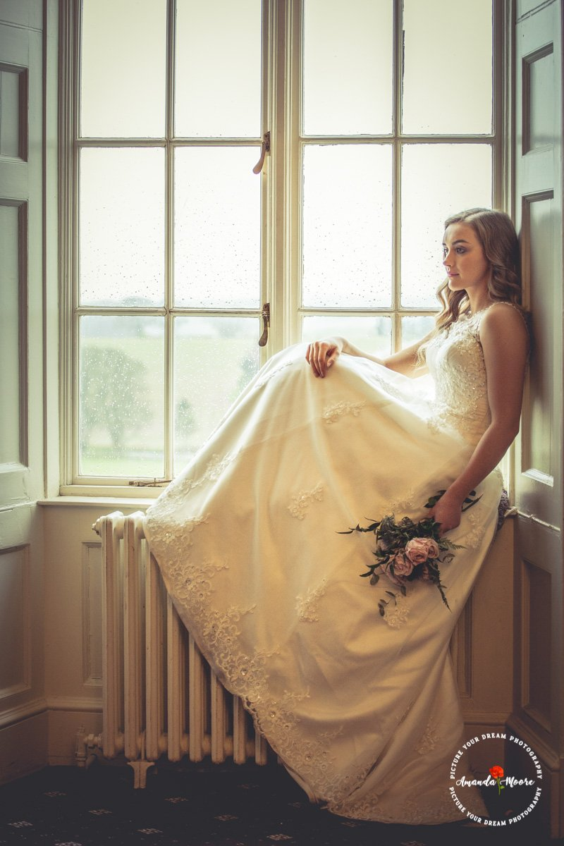 beautiful bride on windowsill wedding photograph