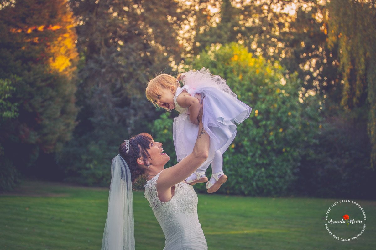 Bride plays with little girl in wedding photo