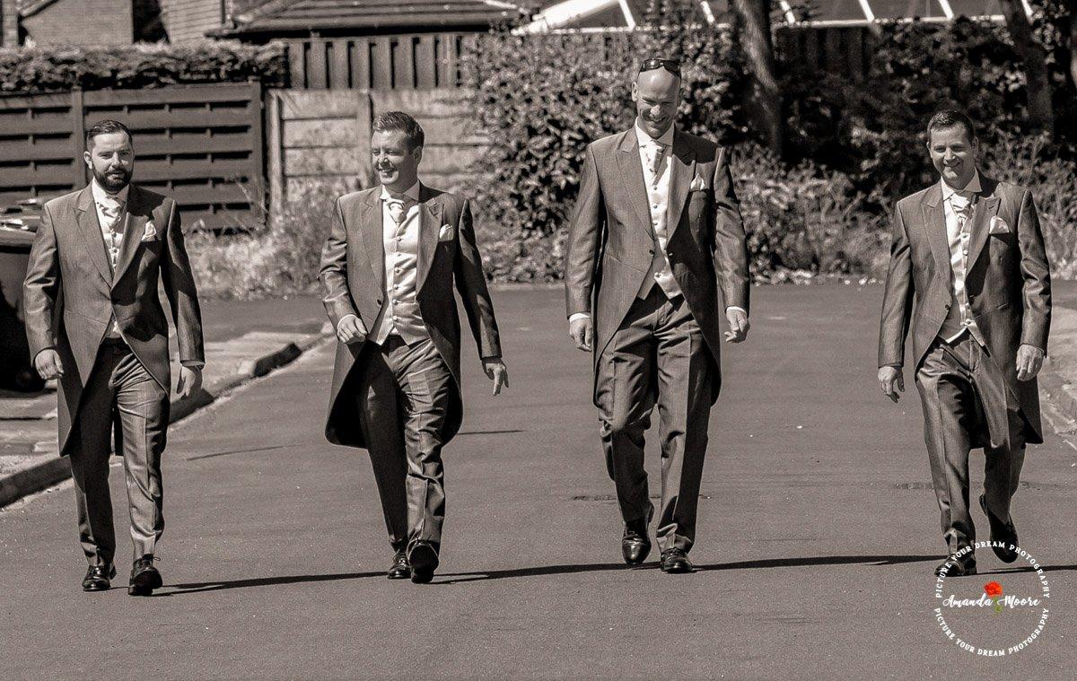groom and groomsmen walking down the street